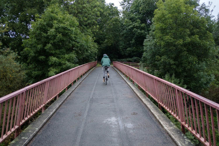 Rear view of woman riding bicycle on footbridge