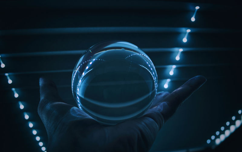 Cropped image of hand holding crystal ball against illuminated ceiling