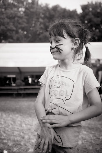 Girl with face paint standing outdoors