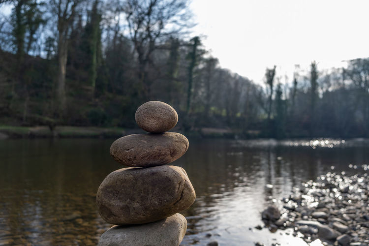 The top of a stack of balancing stones with a river in the background