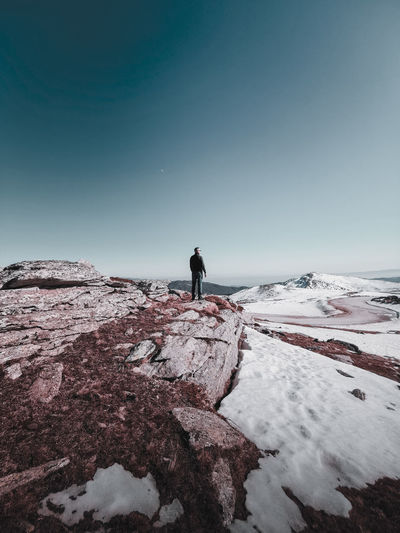 Man standing on rock looking at snowcapped mountain against sky