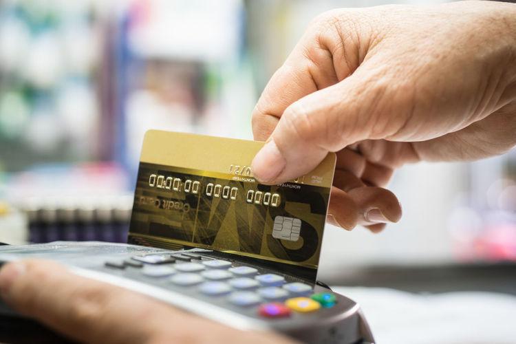 Close-up of hand swiping credit card