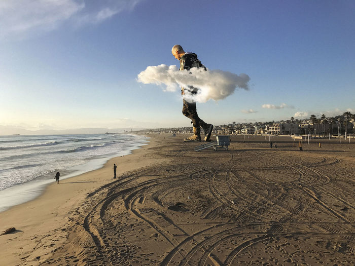 Surreal image of a giant man walking through clouds. Giant Beach Clouds Day Full Length Incidental People Land Leisure Activity Lifestyles Men Motion Nature One Person Outdoors Real People Sand Sea Skill  Sky Sport Surreal Water