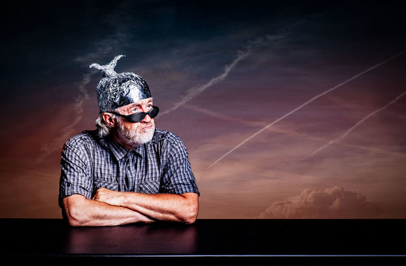 Man looking away while wearing foil hat against sky