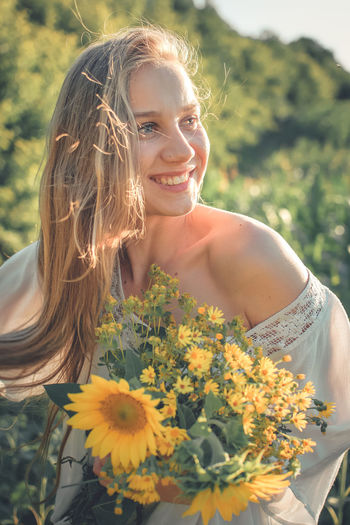 Portrait of smiling young woman with yellow flower