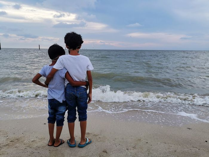 Rear view of boys standing on beach against sky