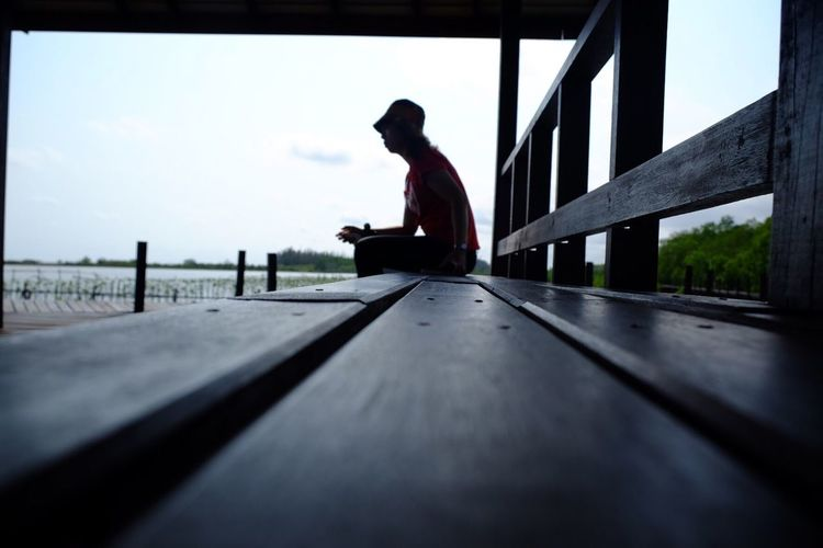 Surface level view of woman sitting on bench