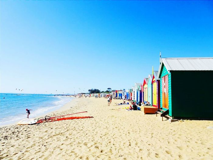 Colorful Huts At Sandy Beach Against Blue Sky