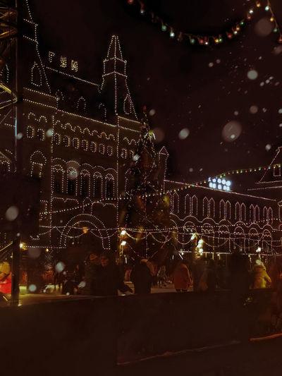 People on illuminated christmas lights at night