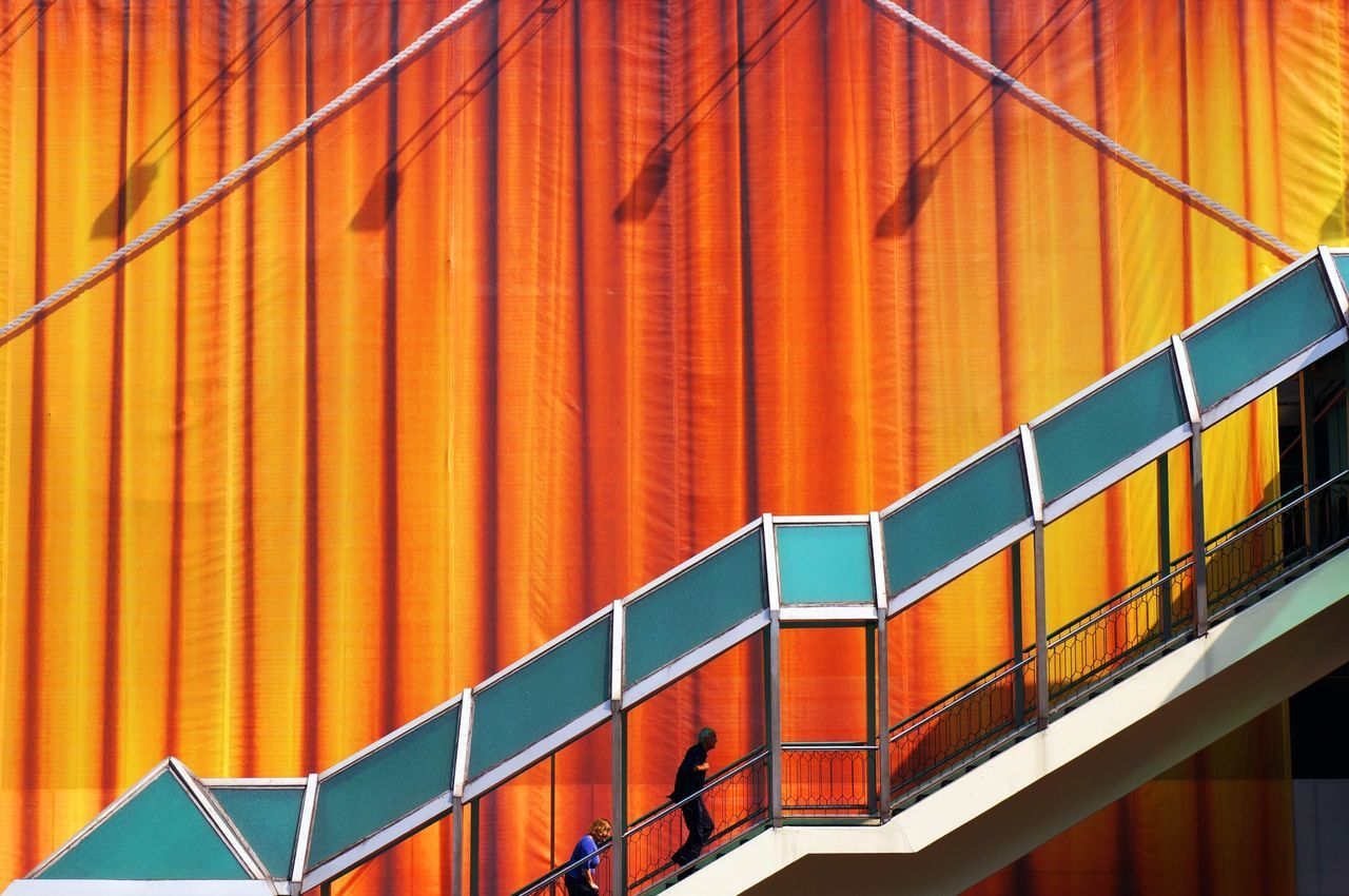 Elevated walkway against large orange curtains