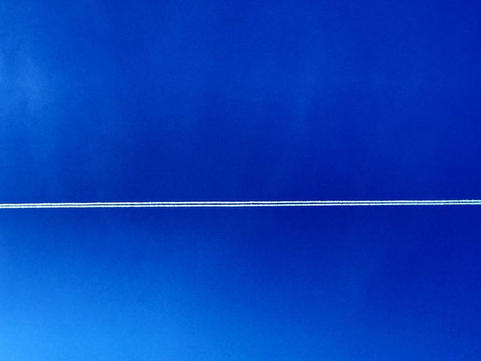 Low angle view of vapor trail against blue sky