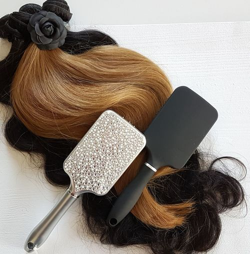 Directly above shot of wig and hairbrushes on table