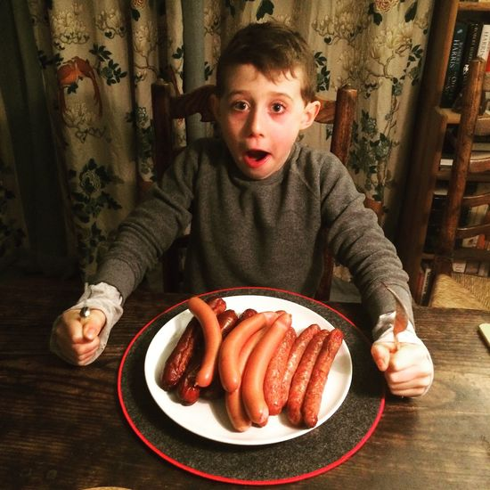 Seven year old boy with a large plate of sausages, Vienna, Austria. Food Table One Boy Only One Person Real People Unhealthy Eating Childhood Sausages! Pork Sausage Vienna Austria Indoors