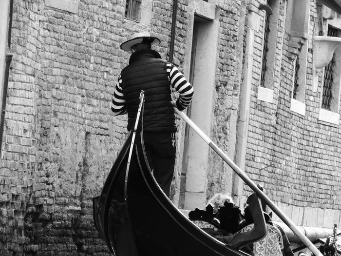 Rear view of man with umbrella in canal