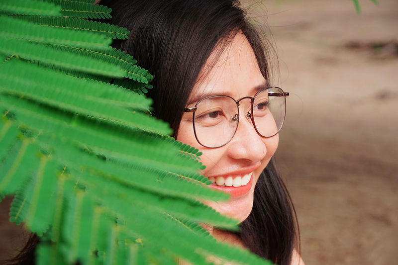 Young woman wearing eyeglasses while looking away by plants