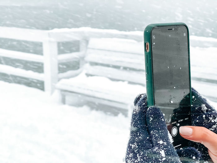 Person holding smart phone during winter