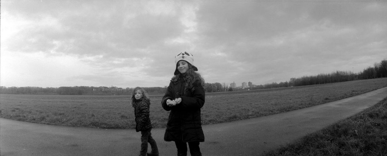 Sisters Playing On Road Against Cloudy Sky