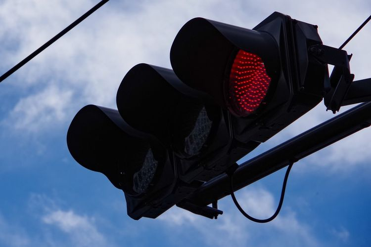 Low Angle View Of Road Signal Against Cloudy Sky