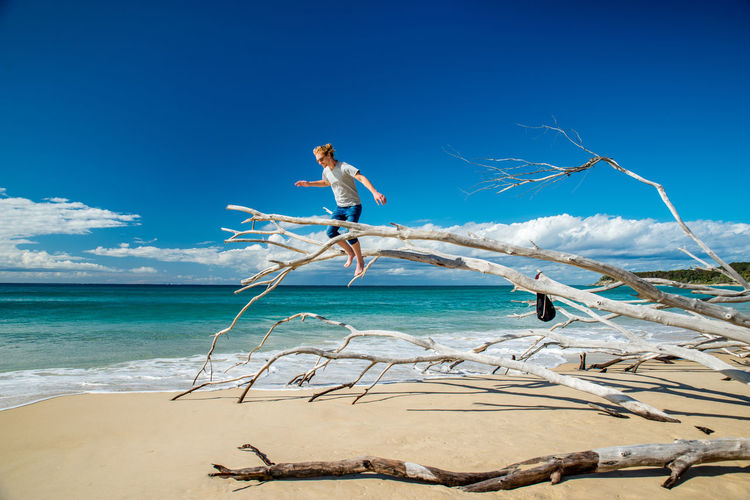 Low Angle View Of Man Standing On Dead Tree Over Sea