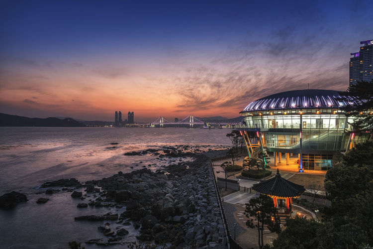 Dongbaek island and Gwangan bridge at sunset in Busan city in Korea. Architecture Beach Building Exterior Built Structure City Cloud - Sky Dusk Illuminated Incidental People Island; Urban; Asia; Cityscape; Nurimaru; Dongbaek; Korea; Bridge; Busan; South; Apec; Gwangan; City; Land Modern; Architecture; House; Asian; Pusan; Night Nature Orange Color Outdoors Scenics - Nature Sea Sky Skyline; Haeundae; Sky; Water; Landscape; Reflection; Sunset Sunset; Travel; Sea; Scenic; Landmark; Panorama; Travel Destinations Water