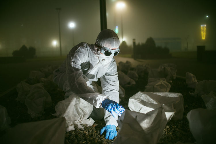 Scientist wearing protective workwear working outdoors at night