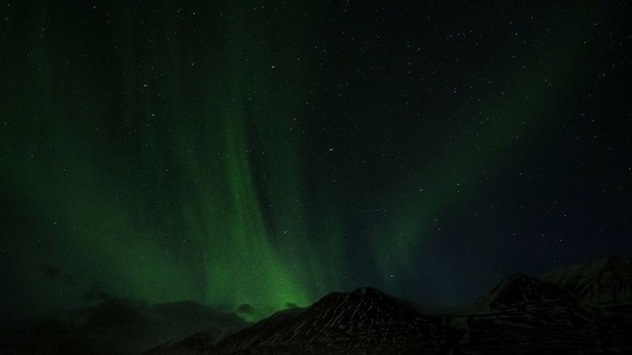 Low angle view of mountain against  aurora at night