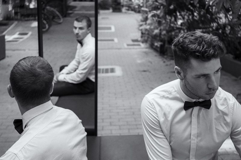 Well Dressed Men Sitting On Bench With Reflection In Mirror