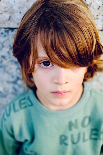 Close-up portrait of boy against wall
