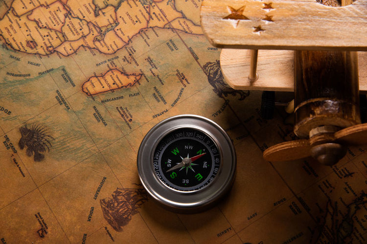 High angle view of compass with toy on table