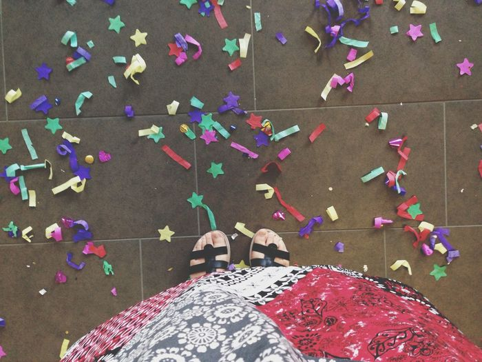 Low Section Of Person Standing By Confetti On Footpath