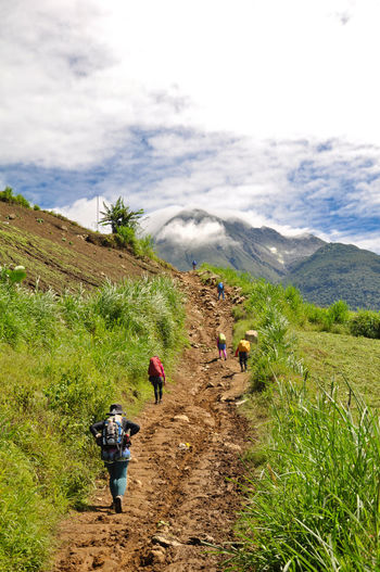 Rear View Of Hikers Walking On Mountain Trail Against Sky
