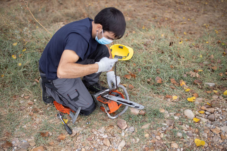 High angle view of man wearing mask holding chainsaw on field