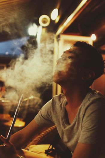 Young Man Smoking While Sitting In Bar