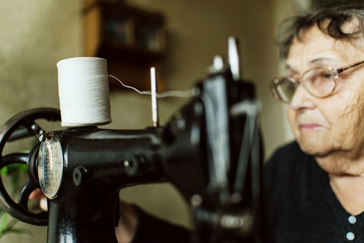 Close-Up Of Senior Woman With Sewing Machine At Home