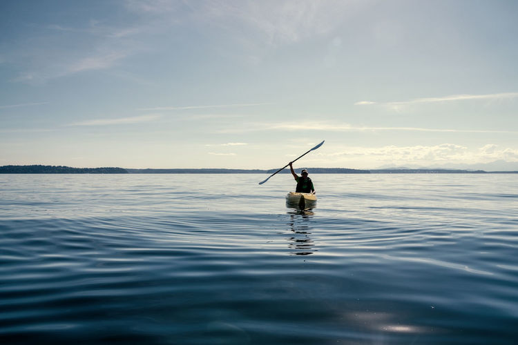 Silhouette man kayaking in sea against sky