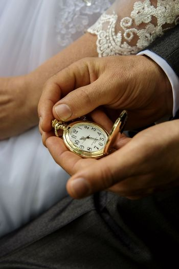 Midsection of groom holding pocket watch by bride