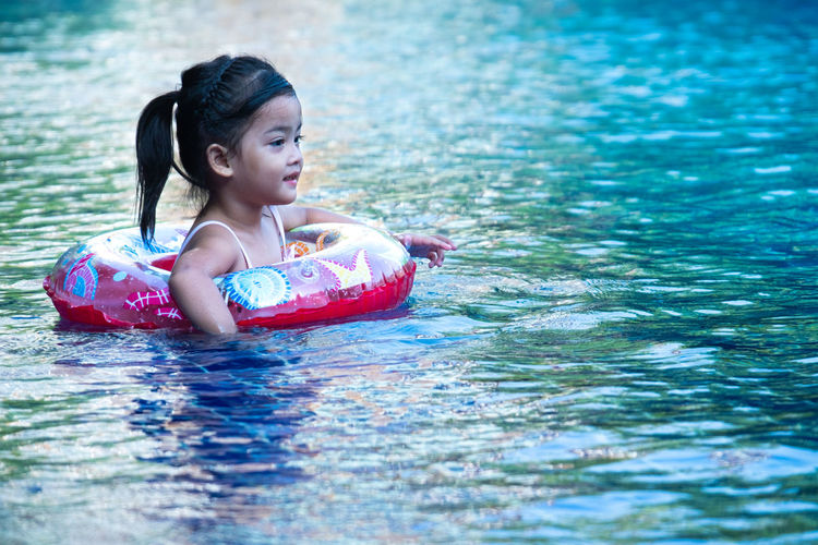 Portrait of cute little asian girl having fun in swimming pool, floating in blue refreshing water with colurful rubber ring Girl Kid Swimming Pool Life Ring Water Child Fun Play Young Outdoor Cute Happy Joy Enjoy Relax Float Blue Summer Vacation Lifestyle Swim Holiday Wet Childhood Activity Fresh Leisure Healthy Refreshing Caucasian Sunlight Little Rubber Sun Happiness Sport Relaxation Smiling Nature Beauty Family Asian  Aqua Funny Floating Liquid Playful Smile