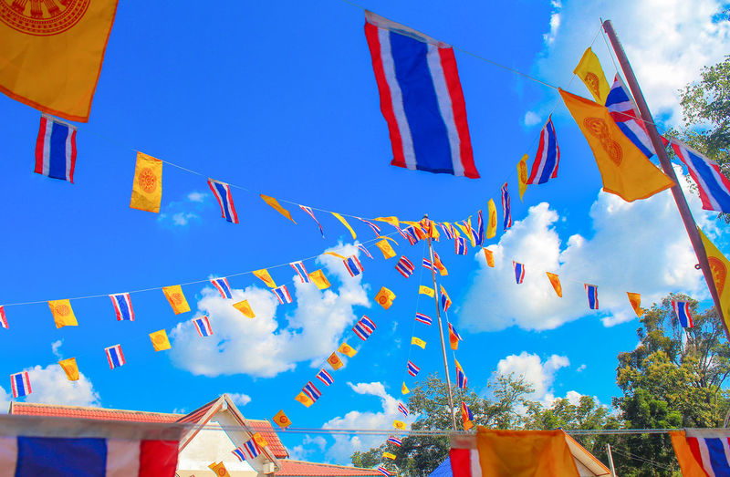 Low angle view of thai flags against sky