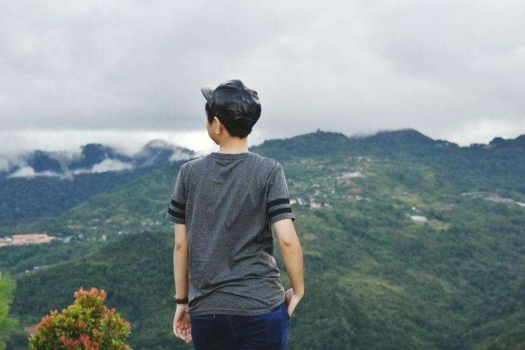 Rear view of person standing on mountain against cloudy sky