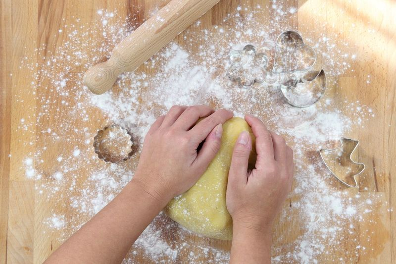 Cropped Hands Kneading Dough On Wooden Table