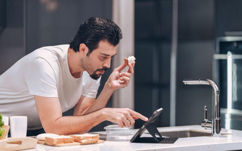 Young man spending time on their tablet on morning in the kitchen