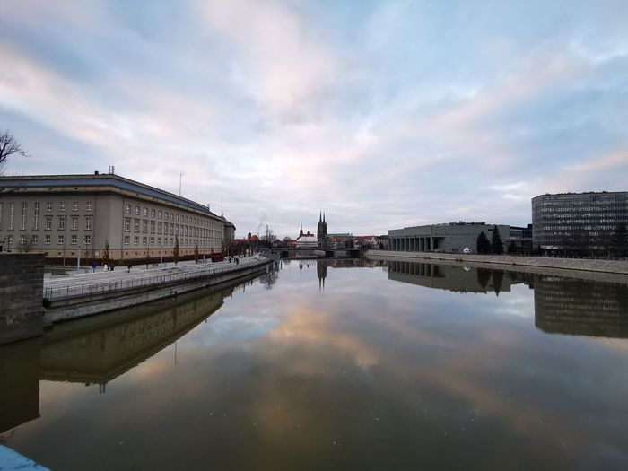 The government building of wroclaw in poland from the view over the oder with pastel-coloured sky