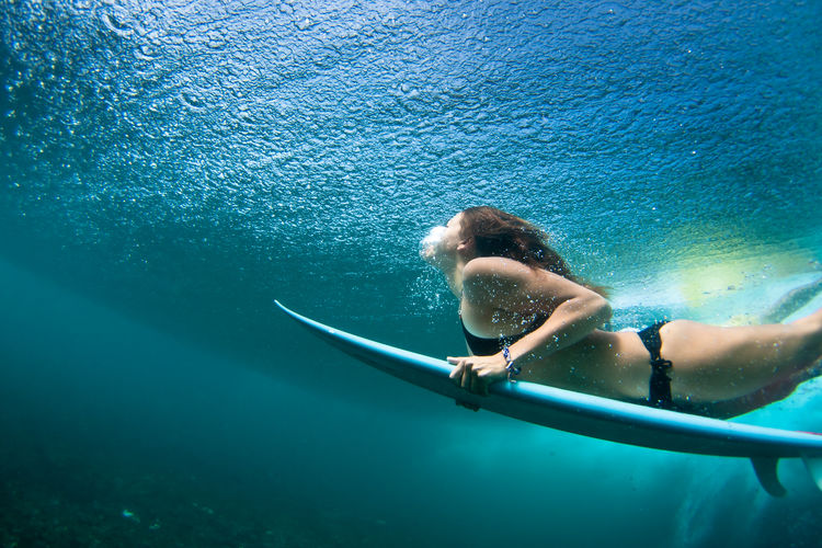 Woman with surfboard board swimming underwater in sea