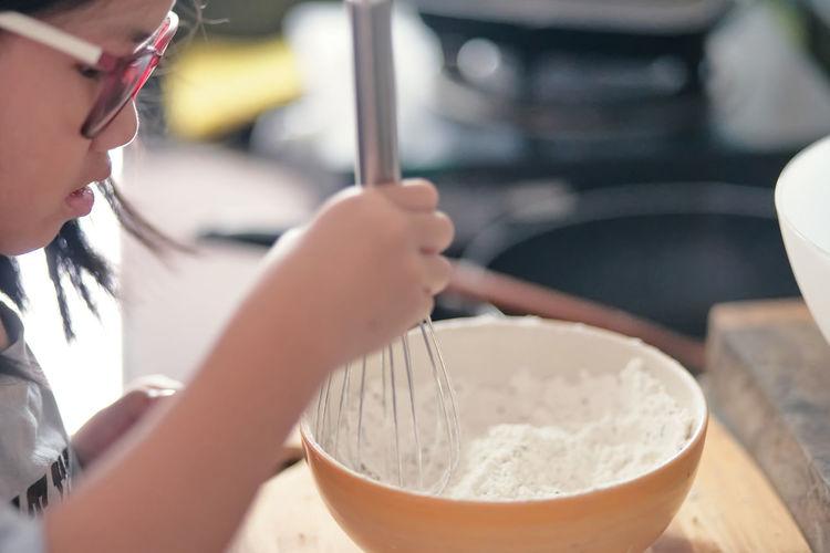 Close-up of cute girl preparing food at home