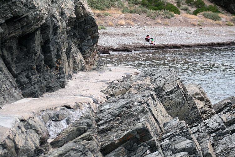 Resting on the pebbles Jagged Rocks Beach Cove Woman And Child On Beach Cliffs