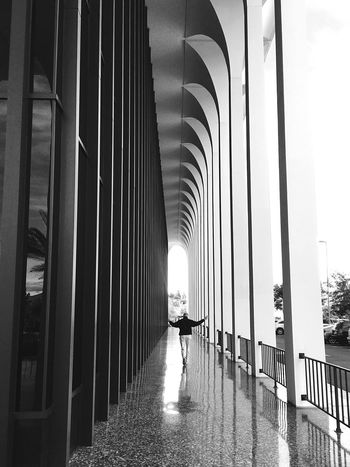Arches and reflections Real People Full Length Lifestyles Architecture Built Structure Rear View One Person Walking Indoors  Arches Sixties Style Public Places Architecturephotography Architectural Column B&w Street Photography Streetphotography dDay tThe Way Forward Reflections And Shadows The Architect - 2017 EyeEm Awards