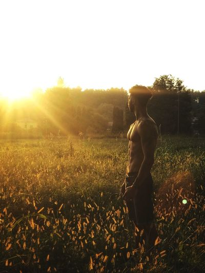 Rear view of man standing on field against bright sun
