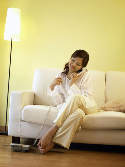 woman relax at sofa using phone At Home Domestic Life Sitting Adults Only Casual Clothing Communication Cushion Day Floor Lamp Front View Full Length Home Interior Indoors  Landline Phone Leisure Activity Lifestyles Living Room One Person One Woman Only Only Women People Sitting Smiling Sofa Young Adult