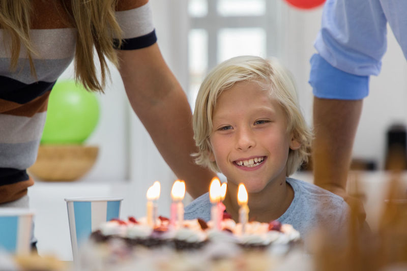 Smiling boy celebrating birthday Birthday Birthday Cake Birthday Candles Bonding Cake Candle Casual Clothing Celebration Childhood Domestic Life Elementary Age Family Food And Drink Indoors  Indulgence Lifestyles Mother Real People Sweet Food Table Togetherness