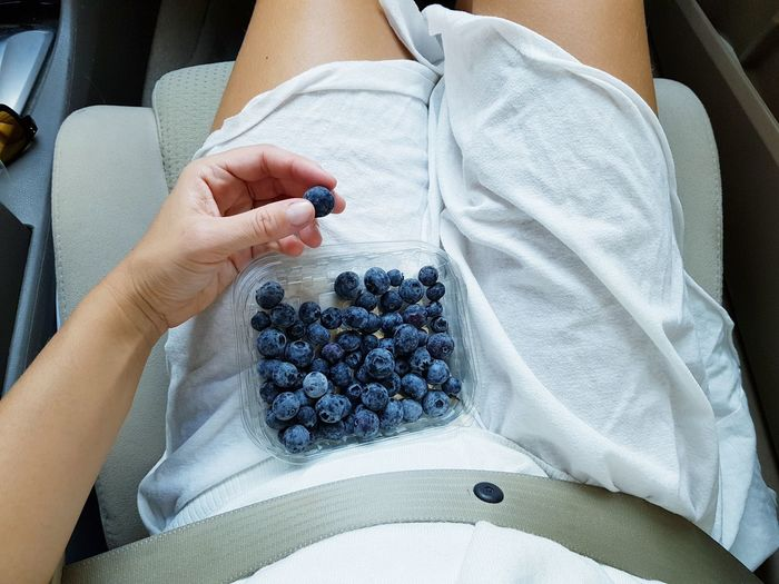 Directly above shot of woman holding blueberry while sitting on car seat